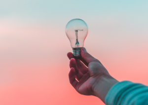 A hand holding a lightbulb